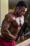 做三头肌的爱好健美者重量级的锻炼与缆绳 图库摄影