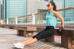 做三头肌长凳的适合的妇女浸洗锻炼,当听到在耳机时的音乐 解决在城市的健身女孩 免版税库存照片