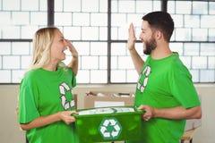 做上流五的微笑的志愿者,当拿着容器时 免版税库存照片