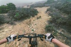 做下坡用她的登山车的少妇 免版税库存图片