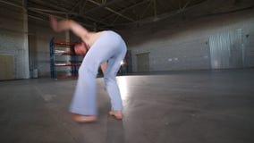 做不同的capoeira元素的一个人-停留在他的手上和做车轮-在有水泥地板的屋子里 股票视频