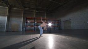 做不同的capoeira元素的一个运动人-翻筋斗在他的头,不用手-在有混凝土的屋子里 股票录像