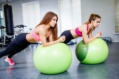 做与一个大绿色健身球的健身、体育、训练和生活方式概念两少妇体育运动在健身房 免版税库存图片