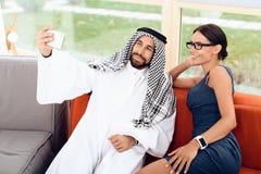 做与一个女孩的阿拉伯商人selfie长沙发的 库存图片
