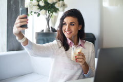 做与一台手机照相机的妇女自画象在拍照片的餐馆在巧妙的电话 库存照片