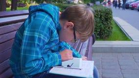 做与一本课本和一种片剂的家庭作业在户外男小学生的画象 影视素材