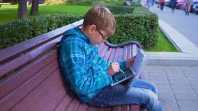 做与一本课本和一种片剂的家庭作业在户外男小学生的画象 股票录像