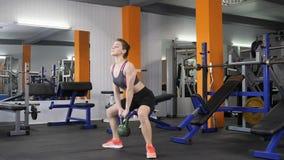 做与一kettlebell的年轻美丽的运动的女孩被衡量的蹲坐在健身房 Loopable 股票视频