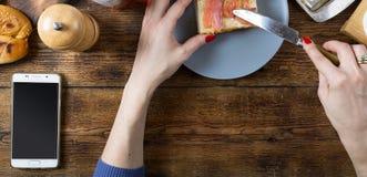 做与三文鱼和黄油的妇女一个三明治 顶面veiw 免版税图库摄影