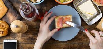 做与三文鱼和黄油的妇女一个三明治 顶面veiw 免版税库存图片