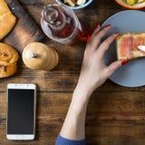 做与三文鱼和黄油的妇女一个三明治 顶面veiw 图库摄影