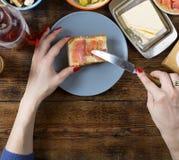 做与三文鱼和黄油的妇女一个三明治 库存照片