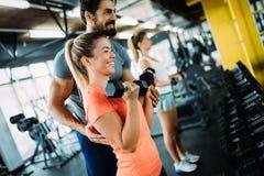 做与个人教练员的年轻美丽的妇女锻炼 免版税库存照片