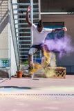 做与五颜六色的holi粉末的溜冰板者一次轻碰 免版税库存图片