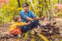 做与他的儿子的愉快的父亲烤肉在一秋天天 图库摄影