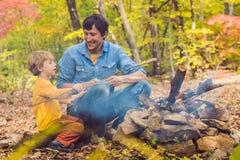 做与他的儿子的愉快的父亲烤肉在一秋天天 免版税库存图片