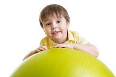 做与健身球的儿童男孩健身锻炼 免版税库存照片