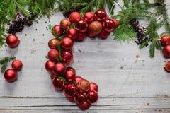 做与冷杉分支和装饰红色球的圣诞节花圈阶段顶视图在木土气桌面 免版税图库摄影