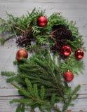 做与冷杉分支和装饰红色球的圣诞节花圈阶段顶视图在木土气桌面 库存图片