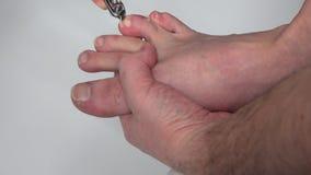做与切割工具的手修脚在有长的钉子的腿 股票录像