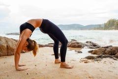 做与后边海洋的妇女瑜伽 库存图片
