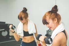 做与哑铃的亚裔少女exrecises在健身房,看她的身体 库存照片