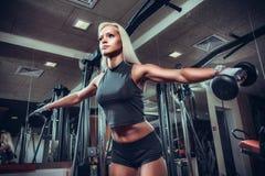 做与哑铃的健身妇女锻炼在健身房 免版税库存图片