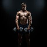 做与哑铃的坚强和力量爱好健美者锻炼 免版税库存图片