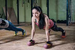 做与哑铃的坚强的适合妇女俯卧撑在健身房的锻炼期间 免版税库存图片