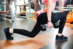 做与哑铃的女子运动员蹲坐在健身房 库存照片