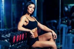 做与哑铃的好性感的妇女锻炼在健身房 免版税库存图片