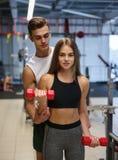 做与哑铃的妇女锻炼在健身房背景 帮助健身俱乐部的一位个人教练员一个客户 免版税库存图片