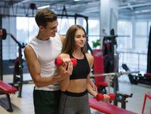 做与哑铃的妇女锻炼在健身房背景 帮助健身俱乐部的一位个人教练员一个客户 免版税库存照片