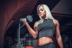 做与哑铃的妇女锻炼在健身房 免版税库存照片