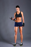 做与哑铃的少妇锻炼 免版税库存图片