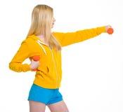 做与哑铃的少年女孩锻炼 免版税库存图片