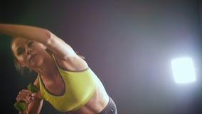 做与哑铃的年轻健身妇女训练在手上-有吸引力的模型在演播室 股票录像