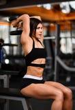 做与哑铃的年轻女运动员举的锻炼 库存图片