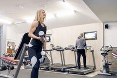 做与哑铃的年轻美丽的白肤金发的妇女力量锻炼在健身房 体育,健身,体型,训练,锻炼 免版税库存照片