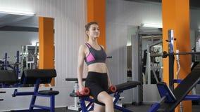做与哑铃的年轻美丽的运动的女孩刺在健身房 Loopable 影视素材