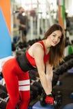 做与哑铃的年轻美女锻炼在健身房 高兴的微笑的女孩享用与她的训练过程 免版税库存照片