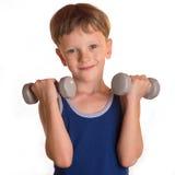做与哑铃的男孩蓝色衬衣锻炼在白色backgro 免版税库存图片