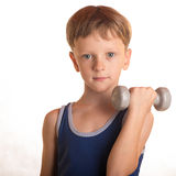 做与哑铃的男孩蓝色衬衣锻炼在白色backgro 库存照片