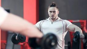 做与哑铃的肌肉爱好健美者锻炼在健身房 免版税库存照片