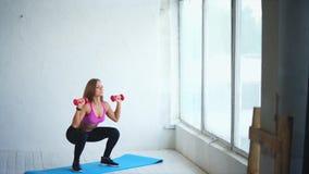做与哑铃的年轻健身教练员深刻的蹲坐在健身俱乐部 影视素材