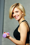 做与哑铃的年轻愉快的适合妇女锻炼 图库摄影