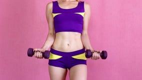 做与哑铃的年轻运动女孩锻炼在桃红色背景的一家体育俱乐部 股票视频
