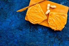 做与坚果浆糊的多士 两枚toastes、刀子和坚果在蓝色背景拷贝空间 免版税库存照片