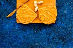 做与坚果浆糊的多士 两枚toastes、刀子和坚果在蓝色背景拷贝空间 图库摄影