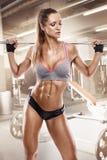 做与大哑铃的好性感的妇女锻炼在健身房, retouche 免版税库存照片